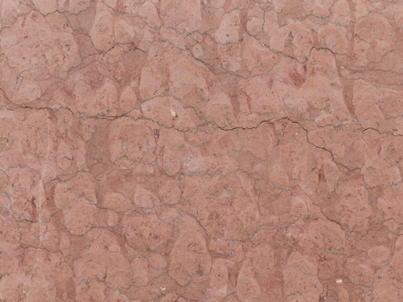 brown granite: large heavy dark red brown granite stone with cracks and stains Stock Photo