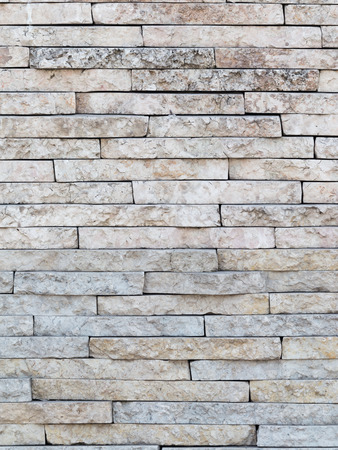porous brick: old wall of beige marble with gray stone, stacked like bricks