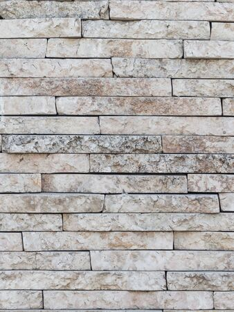 porous brick: wall of marble beige with pink old stone stacked like bricks