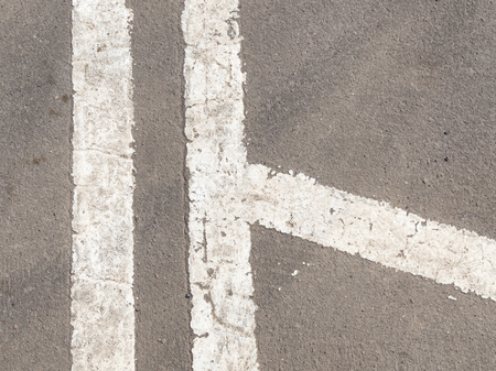 security gap: white markings on the old dirty gray asphalt