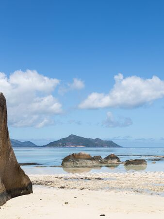 brown granite: big brown granite stone in a calm sea, the islands on the horizon on a beautiful Seychelles beach with white coral sand and the blue sky with white cumulus clouds