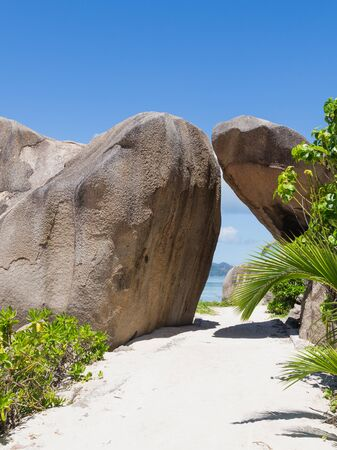 brown granite: big brown granite stones create a tunnel on a beautiful white coral sand from the track on the beach on the island of La Digue, Seychelles Stock Photo
