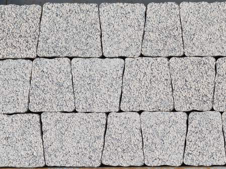 trapezoid: beautiful wall of artificial light gray stones in the shape of a trapezoid, made of concrete, for finishing the exterior facades of buildings and tracks Stock Photo