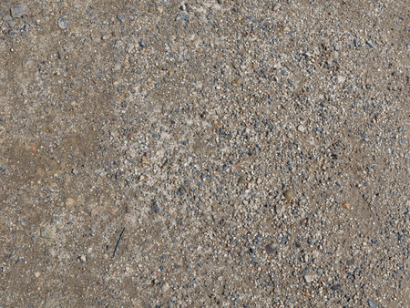 interspersed: old gray dirt road interspersed with fine granite gravel on the street of the village