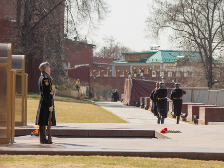 Moscow - April 12, 2015: Change of the guard of honor at the eternal flame at the Tomb of the Unknown Soldier in Alexander Garden at the Kremlin in memory of those killed in World War II and lay red carnations on the granite stone April 12, 2015, Moscow,