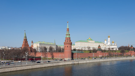 dovetail: Moscow - April 12, 2015: View of the Kremlin Embankment on a sunny day in early spring, people walking and cars go along the Kremlin walls and clearly visible architectural ensemble of the Moscow Kremlin April 12, 2015, Moscow, Russia Editorial