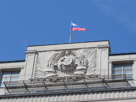 duma: Moscow - April 12, 2015: The Russian flag flew over the building of the State Duma and the bas-relief emblem of the USSR against the blue sky on a clear day April 12, 2015, Moscow, Russia