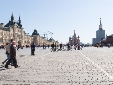 dovetail: Moscow - April 12, 2015: Citizens and tourists walking on the pavement on the Red Square in Moscow Spasskaya Tower opened after restoration work in good weather in early spring April 12, 2015, Moscow, Russia