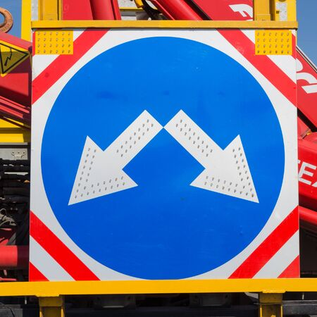 roadworks: round blue road sign with white arrow, built-in LED lights and reflective red, silver and yellow paint on the street where roadworks