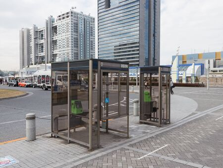 directorio telefonico: Tokio - 03 de febrero 2015: Dos cabinas telef�nicas de vidrio para las personas sanas y personas con discapacidad en la zona tur�stica moderna de 3 de febrero de 2015, Odaiba, Tokio, Jap�n
