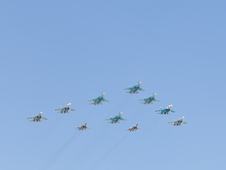 aerobatics: Moscow - May 7th, 2015: Military aircraft painted in the blue sky aerobatics in honor of the seventieth birthday of fascism shall meet you at the rehearsal of the Victory Parade on the background of blue sky May 7, 2015, Moscow, Russia