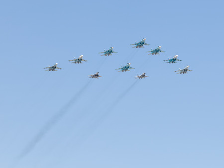 aerobatics: Moscow - May 7th, 2015: Military aircraft painted in the sky aerobatics in honor of the seventieth birthday of fascism shall meet you at the rehearsal of the Victory Parade on the background of blue sky May 7, 2015, Moscow, Russia Editorial