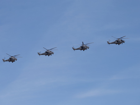 fixed wing aircraft: Moscow - May 7th, 2015: Four military helicopters Mi-35 flying formation against a blue sky with clouds 7, 2015, Moscow, Russia Editorial