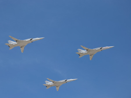 may fly: Moscow - May 7th, 2015: aircraft Tu-22M3 missile systems on the fly against a blue sky with clouds May 7, 2015, Moscow, Russia