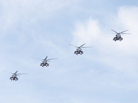 fixed wing aircraft: Moscow - May 7th, 2015: Four military helicopters Mi-35 flying forward each other against a blue sky with clouds 7, 2015, Moscow, Russia Editorial