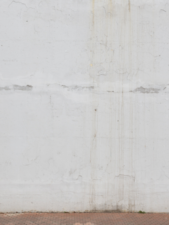 flaky: surface of an old white, jagged walls, painted bright white flaky oil paints and floor of the old paving slabs on the street