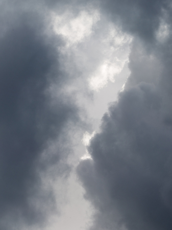 photons: Heavenly vertical landscape with dark gray storm rain cumulus clouds darkened the skies