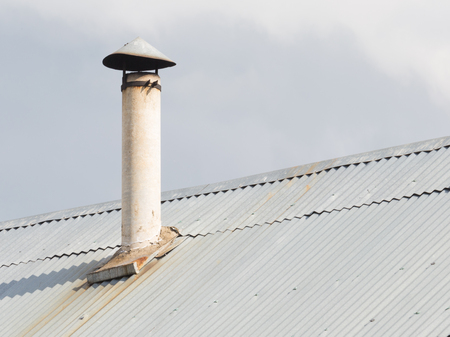 horse pipes: cheap old chimney with headroom of stainless steel and gray roof Stock Photo