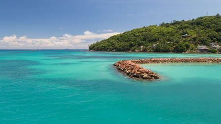 cumulus: Lovely bright horizontal seascape with a breakwater made of stones in a clean transparent blue sea, Seychelles