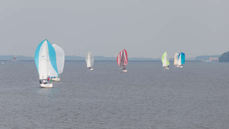 klyazma: Moscow - July 9, 2015: A lot of bright beautiful sailboats on Klyazma reservoir swim summer July 9, 2015, Moscow, Russia Editorial