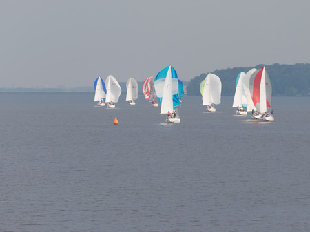 klyazma: Moscow - July 9, 2015: A lot of bright beautiful sailboats on Klyazma reservoir swim in the summer foggy weather in July 9, 2015, Moscow, Russia Editorial