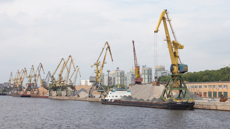 sand harbor: Moscow - July 9, 2015: Large harbor cranes, like giraffes, in the North river port barge loaded with gravel and sand, July 9, 2015, Moscow, Russia