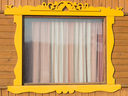casings: box with yellow carved wooden casings and striped closed curtains Stock Photo