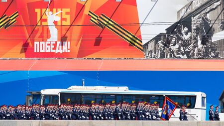a rehearsal: Moscow - May 7th, 2015: Military cadets go to the rehearsal of the Victory Parade in Moscow on a background of bright poster May 7, 2015, Moscow, Russia