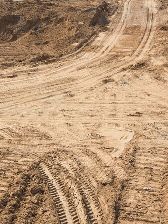 protectors: dirt road with light yellow sand fines on the construction site and traces of protectors of wheels, vertically Stock Photo