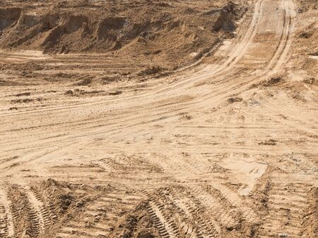 protectors: dirt road with light yellow sand fines on the construction site and traces of protectors of wheels Stock Photo