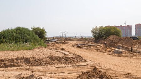 protectors: construction of a new road with light yellow sand fines on the construction site and traces of protectors of wheels Stock Photo