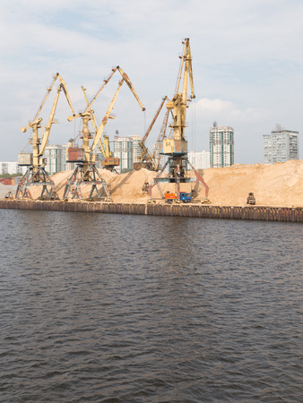 sand harbor: Moscow - June 9, 2015: Harbor cranes in the North river port and a lot of sand to be loaded onto barges June 9, 2015, Moscow, Russia