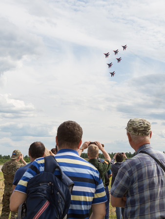 all weather: The Moscow region - 19 June 2015: Spectators take pictures of the airshow demonstration flights of military aircraft MiG-29 beautiful aerobatic team Swifts at the airfield Kubinka June 19, 2015, Moscow Region, Russia