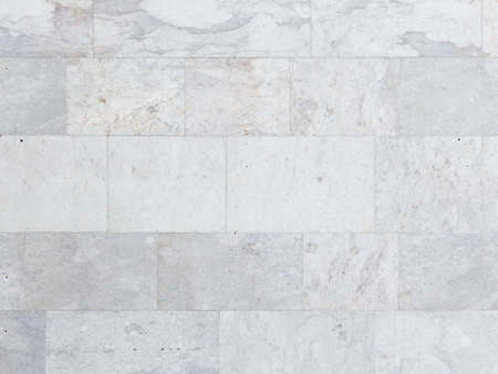 bricks background: Bright old gray wall lined with beautiful marble with variegated streaks