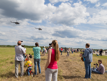 military watch: The Moscow region - 19 June 2015: People watch the demonstration flights of military helicopters at the airfield Kubinka June 19, 2015, Moscow Region, Russia Editorial