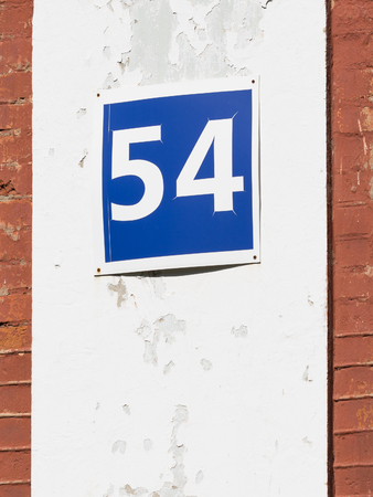 54: bright blue plate with the numbers 54 on metal hanging on the wall with an old plaster Stock Photo