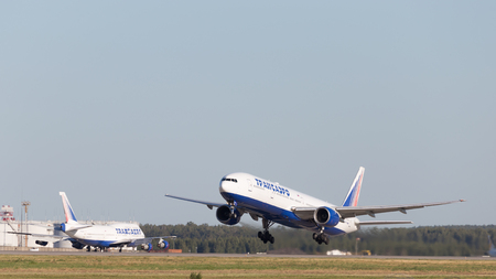 spar: Moscow - August 6, 2015: A powerful passenger jet of the Russian airline Transaero flies to Domodedovo airport and on the background of the runway on Aug. 6, 2015, Moscow, Russia