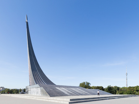 astronautics: Moscow - August 24, 2015: High unusual silver Monument to the Conquerors of Space and guard walks up the steps in the early morning in the summer of August 24, 2015, Moscow, Russia