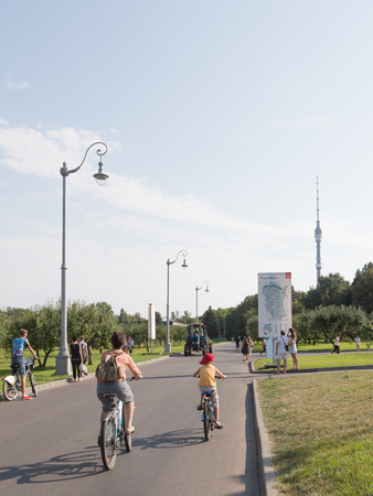 good weather: Moscow - August 13, 2015: Happy adults and children ride bikes in good weather in the summer in the city on August 13, 2015 Exhibition Center, Moscow, Russia