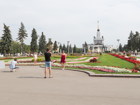 good weather: Moscow - August 13, 2015: Happy adults and children are photographed against the backdrop of the beautiful flower beds and Exhibition Center Pavilion in good weather in the summer in the city of 13 August 2015, Moscow, Russia