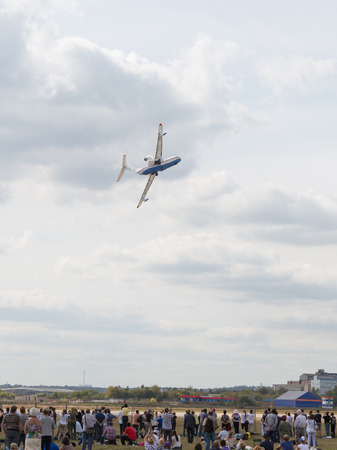 clothes interesting: The Moscow region - August 28 2015: A demonstration flight of the Russian Be-200 aircraft at the international air show Max 2015 and people are watching the flight of August 28, 2015, Zhukovsky, Moscow Region, Russia Editorial