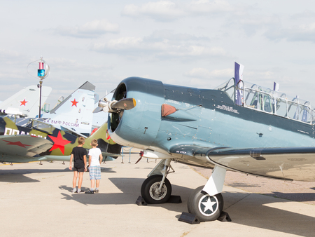 clothes interesting: The Moscow region - August 28 2015: Two boys considering the exposure of vintage aircraft at the air show in Zhukovsky Max August 28, 2015, Zhukovsky, Moscow Region, Russia Editorial