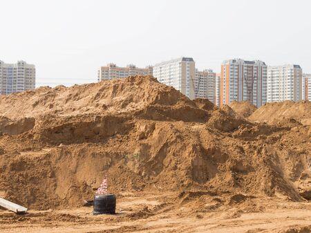 Bau einer neuen Straße mit der Verlegung der Rohre und Dachrinnen, und eine Menge von gelben Sand auf einer Baustelle in einem neuen Bereich
