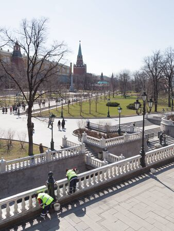 good weather: Moscow - April 12 2015: Cleaners clean and a lot of people walking in the Alexander Garden near the Kremlin in good weather in the spring of April 12, 2015, Moscow, Russia