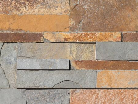 not painted: wall made of natural decorative stone with a rough gray and brown textured surface similar to rust Stock Photo