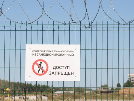 unauthorized: The Moscow region - August 20, 2015: A warning sign saying unauthorized access is prohibited, and a symbol on a green fence with barbed wire at the airport Domodedovo August 20, 2015, Moscow Region, Russia