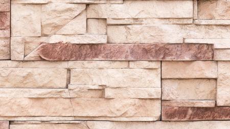 par�?s: una pared de color beige y marr�n fachada de piedra artificial con superficies fracturadas �speras, establecido como un ladrillo Foto de archivo