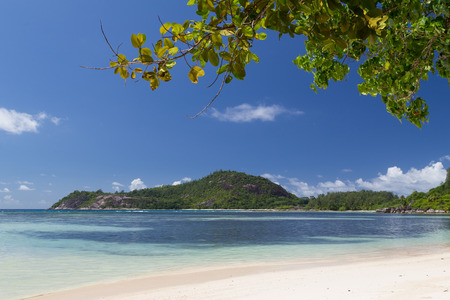 clear waters: Lovely bright seascape with white sand, green mountains with tropical plants and clean clear waters of the Indian Ocean, Seychelles Stock Photo