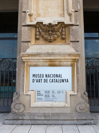 opening hours: Barcelona - October 11, 2015: Information plate of the National Art Museum of Catalonia with the opening hours of the museum on a column of travertine in the classical frame of October 11, 2015, Barcelona, Catalonia, Spain