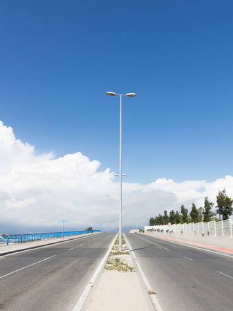 restricting: four-lane asphalt road with lamp posts goes beyond the horizon with blue sky and road signs restricting speed